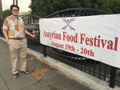 Paul D. Goodman with Assyrian Church Festival sign 15 July 2017