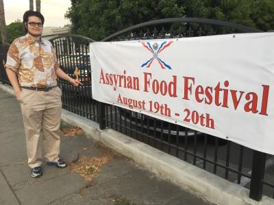 Paul D. Goodman with Assyrian Church Festival sign 15 July 2017